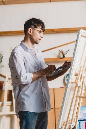 Foto de Apuesto artista mezcla pinturas paleta estando cerca de caballete con lienzo - Imagen libre de derechos