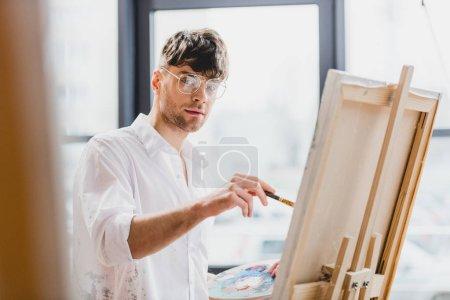 Photo pour Mise au point sélective du bel artiste dans les lunettes en regardant la caméra tout en dessinant sur toile - image libre de droit