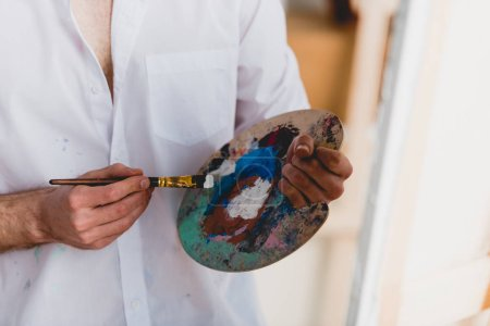 Photo for Partial view of artist in white shirt mixing paints with paintbrush on palette - Royalty Free Image