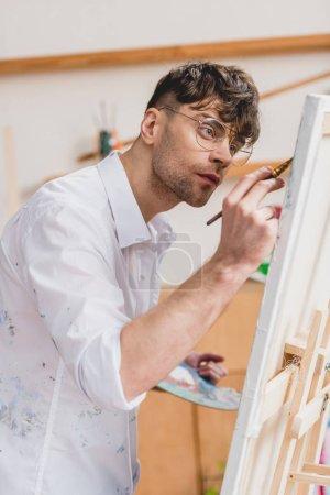 Foto de Artista guapo en camiseta blanca y gafas de pintura sobre lienzo - Imagen libre de derechos
