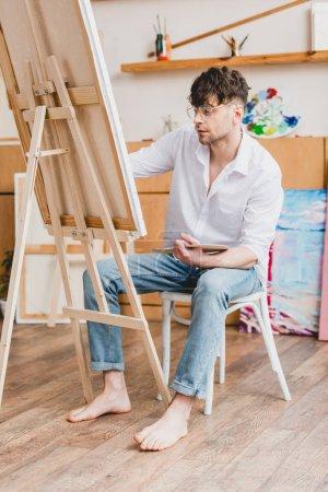 Foto de Artista guapo en camiseta blanca y gafas de pintura sobre lienzo sentado en silla en estudio de pintura - Imagen libre de derechos