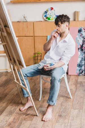 Foto de Artista guapo en camiseta blanca y pantalones vaqueros azul mirando el lienzo en caballete - Imagen libre de derechos
