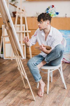 Foto de Concentrado a guapo artista pintando sobre lienzo sentado en silla en Galería - Imagen libre de derechos