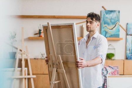 Foto de Enfoque selectivo del guapo artista mirando a cámara mientras está parado en el caballete con lienzo - Imagen libre de derechos