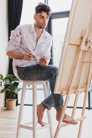 Photo pour Belle artiste en chemise blanche et jeans bleus mélangeant peintures sur palette tout en étant assis au chevalet dans la galerie - image libre de droit