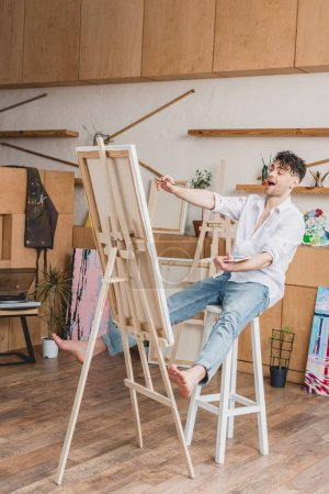 Foto de Artista emocionado sentado en silla alta en caballete con lienzo - Imagen libre de derechos