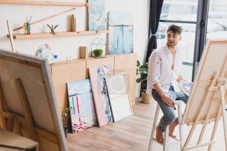Photo pour Foyer sélectif du bel artiste souriant assis sur la chaise haute au chevalet - image libre de droit
