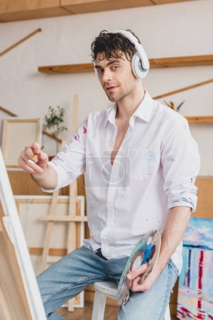 Photo for Selective focus of handsome artist listening music with headphones - Royalty Free Image