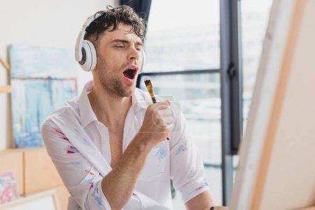 Foto de Enfoque selectivo del guapo artista en auriculares, cantando con pincel - Imagen libre de derechos