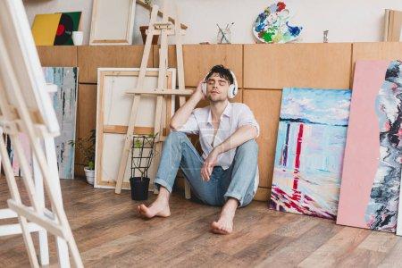 Photo pour Artiste beau casque d'écoute, écoute la musique avec les yeux fermés en étant assis sur le plancher - image libre de droit