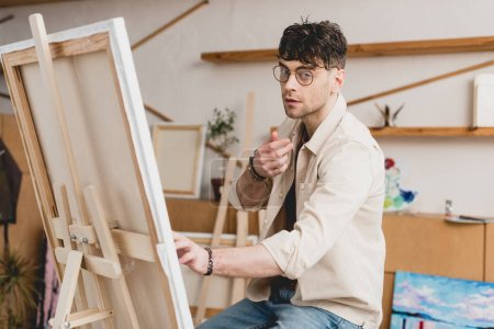 Photo for Handsome artist in eyeglasses sitting near easel with canvas and looking at camera - Royalty Free Image