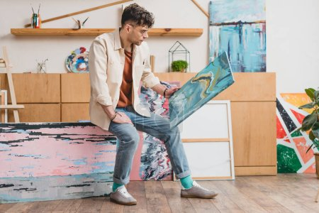 Photo for Handsome artist in pink shirt and blue jeans looking at colorful abstract painting - Royalty Free Image