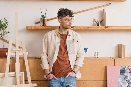 Foto de Apuesto artista en las lentes en la galería de pie con las manos en los bolsillos - Imagen libre de derechos