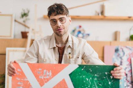 Photo pour Mise au point sélective du bel artiste dans les lunettes tenant l'image et regardant la caméra - image libre de droit