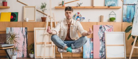 Photo for Panoramic shot of artist with closed eyes levitating in lotus pose in gallery - Royalty Free Image