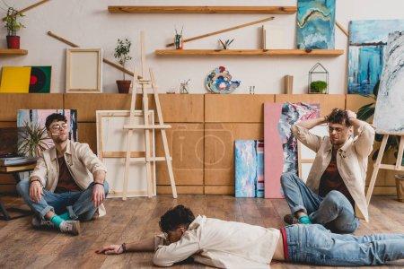 Photo pour Exposition multiple d'artiste dans le mensonge et seating poses dans l'atelier de peinture - image libre de droit