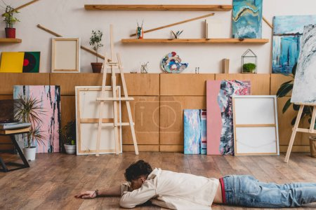 Photo for Artist laying face down on wooden floor in spacious painting studio - Royalty Free Image