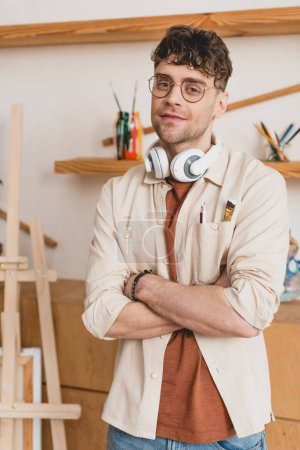Photo for Handsome artist with headphones on neck and crossed arms looking at camera - Royalty Free Image