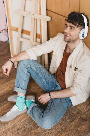 Photo pour Artiste souriant dans les écouteurs assis sur le plancher et l'écoute de musique en studio de peinture - image libre de droit