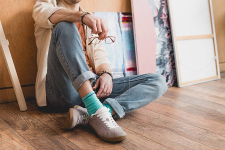 Photo for Cropped view of artist sitting on wooden floor and holding eyeglasses - Royalty Free Image