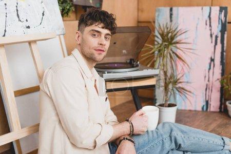 Foto de Artista guapo sosteniendo la taza de café mientras que se sentaba cerca de tocadiscos de vinilo - Imagen libre de derechos