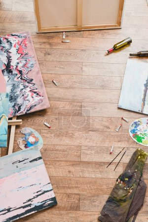 Photo for High angle view of paintings, draw utensils and empty bottles on wooden floor in gallery - Royalty Free Image