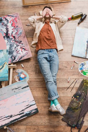 Photo for Overhead view of tired artist lying on wooden floor in painting studio and holding hands on face - Royalty Free Image