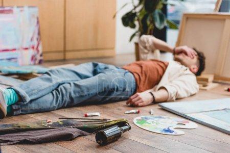 Foto de Selective focus of tired artist lying on floor with hand on face - Imagen libre de derechos