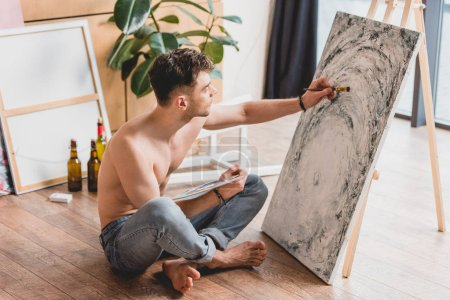 Foto de Hermoso artista semidesnuda sentada con las piernas cruzadas en el piso y pintura cuadro sobre lienzo - Imagen libre de derechos