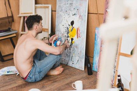 Photo pour Foyer sélectif de l'artiste à moitié nu en jeans bleus assis sur le sol et peinture tableau sur toile - image libre de droit