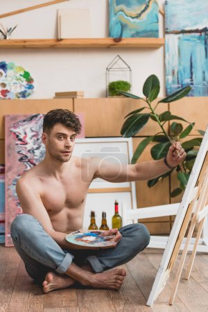 Photo for Handsome half-naked artist holding palette and painting picture on canvas - Royalty Free Image