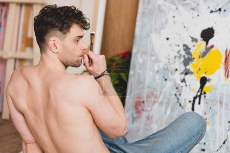 Photo pour Foyer sélectif de beau artiste à moitié nu assis sur le sol en face de la toile avec photo - image libre de droit