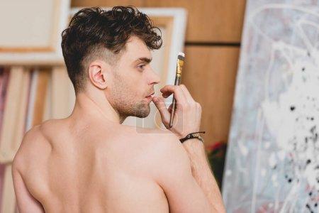 Foto de Enfoque selectivo del guapo artista semidesnuda sosteniendo el pincel - Imagen libre de derechos