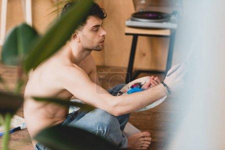 Photo pour Mise au point sélective de réfléchie artiste demi-nu tenant palette - image libre de droit