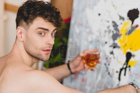 Photo pour Foyer sélectif du bel artiste tenant un verre de whisky et regardant la caméra - image libre de droit