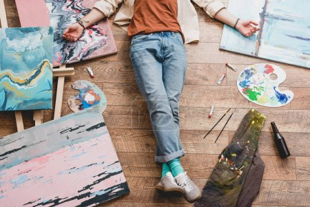 Photo for Partial view of artist lying of floor, surrounded with painting and draw utensils - Royalty Free Image