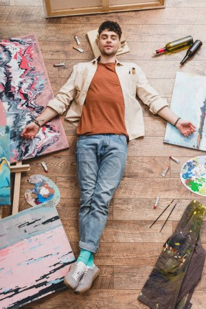 Foto de Tired artist lying of floor, surrounded with paintings and draw utensils, and looking at camera - Imagen libre de derechos