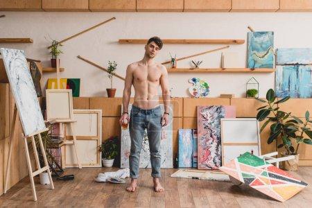 Photo pour Beau artiste à moitié nu en jeans bleus debout dans la galerie spacieuse - image libre de droit
