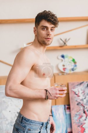Photo for Handsome half-naked artist in blue jeans holding glass of whiskey - Royalty Free Image
