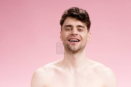 Photo for Good-looking, smiling brunette man looking at camera on pink - Royalty Free Image