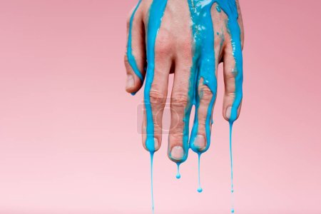 Photo for Cropped view of man with hand in blue paint spills on pink - Royalty Free Image