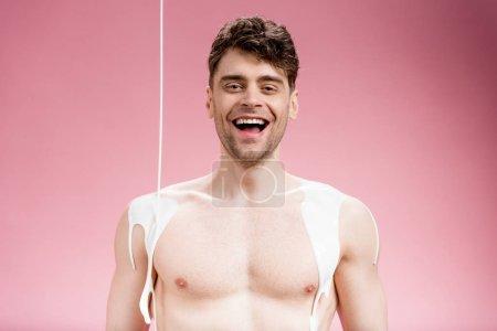 Photo pour Homme souriant avec peinture blanche renverse sur le corps en regardant la caméra sur rose - image libre de droit