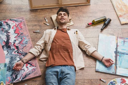 Photo for Exhausted artist lying on floor in painting studio, surrounded by paintings, empty bottles and draw utensils - Royalty Free Image