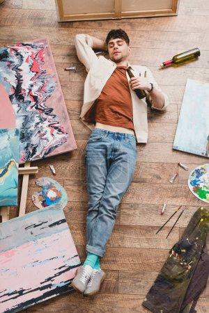 Foto de Vista aérea del artista en suelo y sosteniendo la botella de alcohol - Imagen libre de derechos