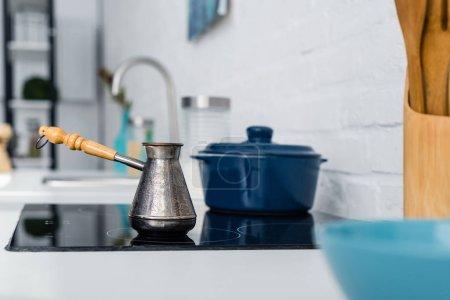 Photo pour Mise au point sélective des turc cezve métal avec poignée sur four dans cuisine - image libre de droit