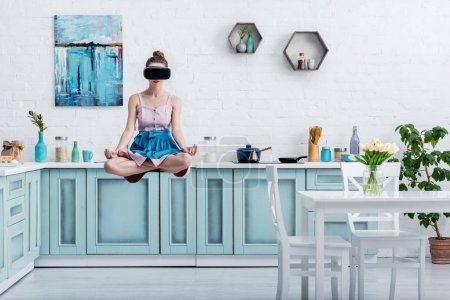 young woman levitating in air in lotus pose and in virtual reality headset