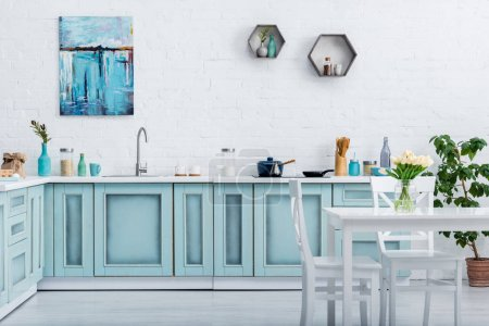 interior of turquoise and white elegant kitchen with kitchenware and decor