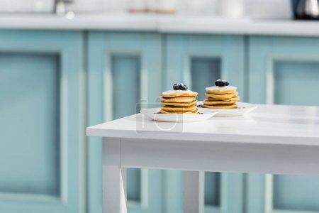 leckere Pfannkuchen mit Zuckerpuder und Blaubeeren in Tellern auf weißem Tisch