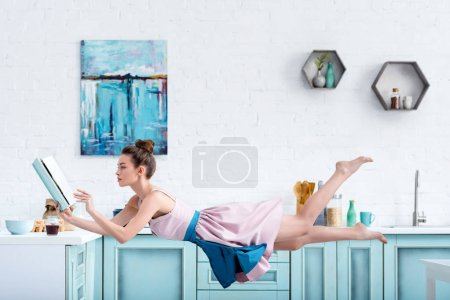Photo for Young concentrated barefoot woman levitating in air while reading recipe in cookbook - Royalty Free Image