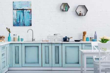 Photo for Interior of modern turquoise kitchen with painting on white brick wall - Royalty Free Image